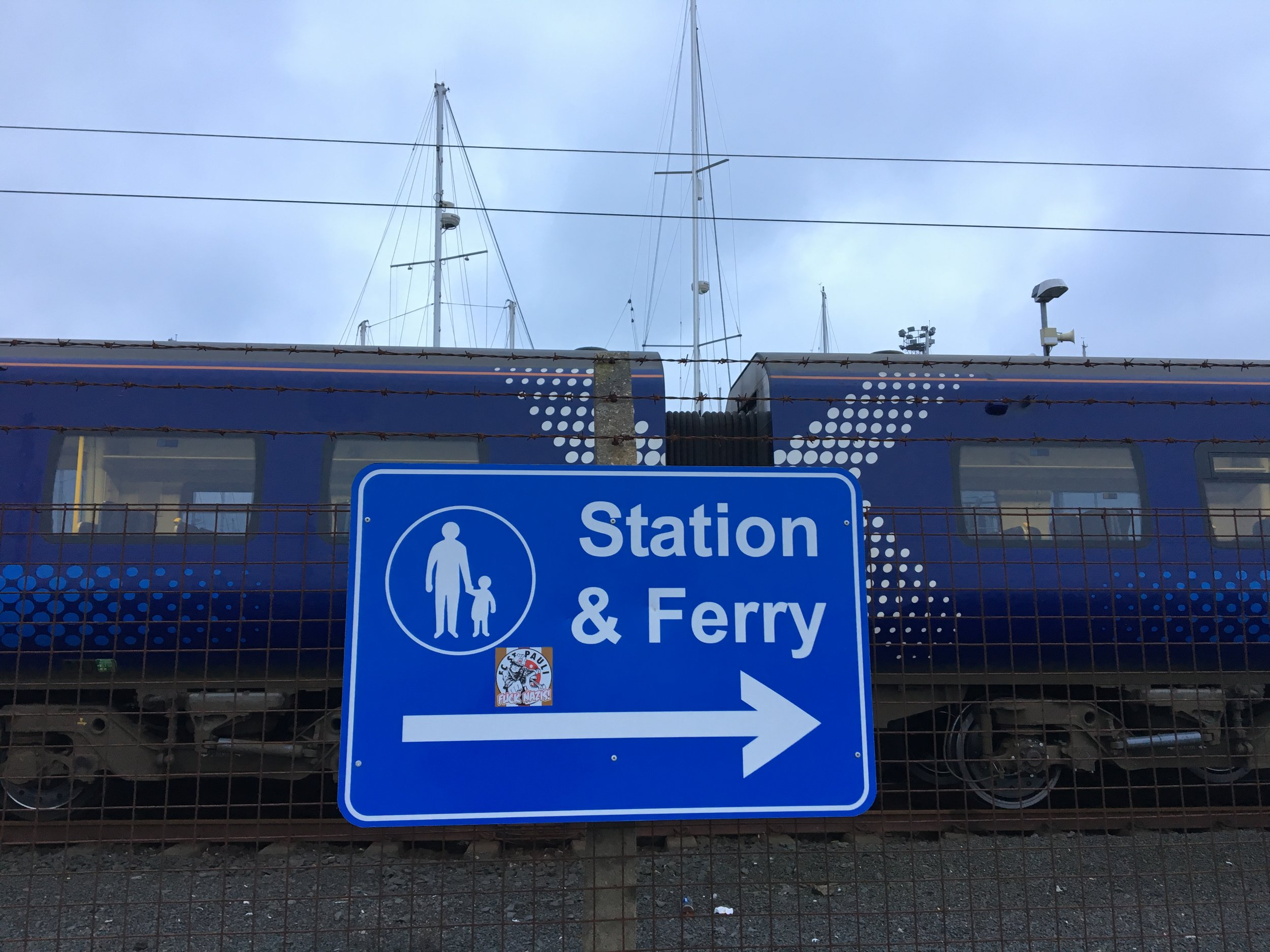 Image shows a sign to the station and ferry terminal near to Ardrossan Harbour