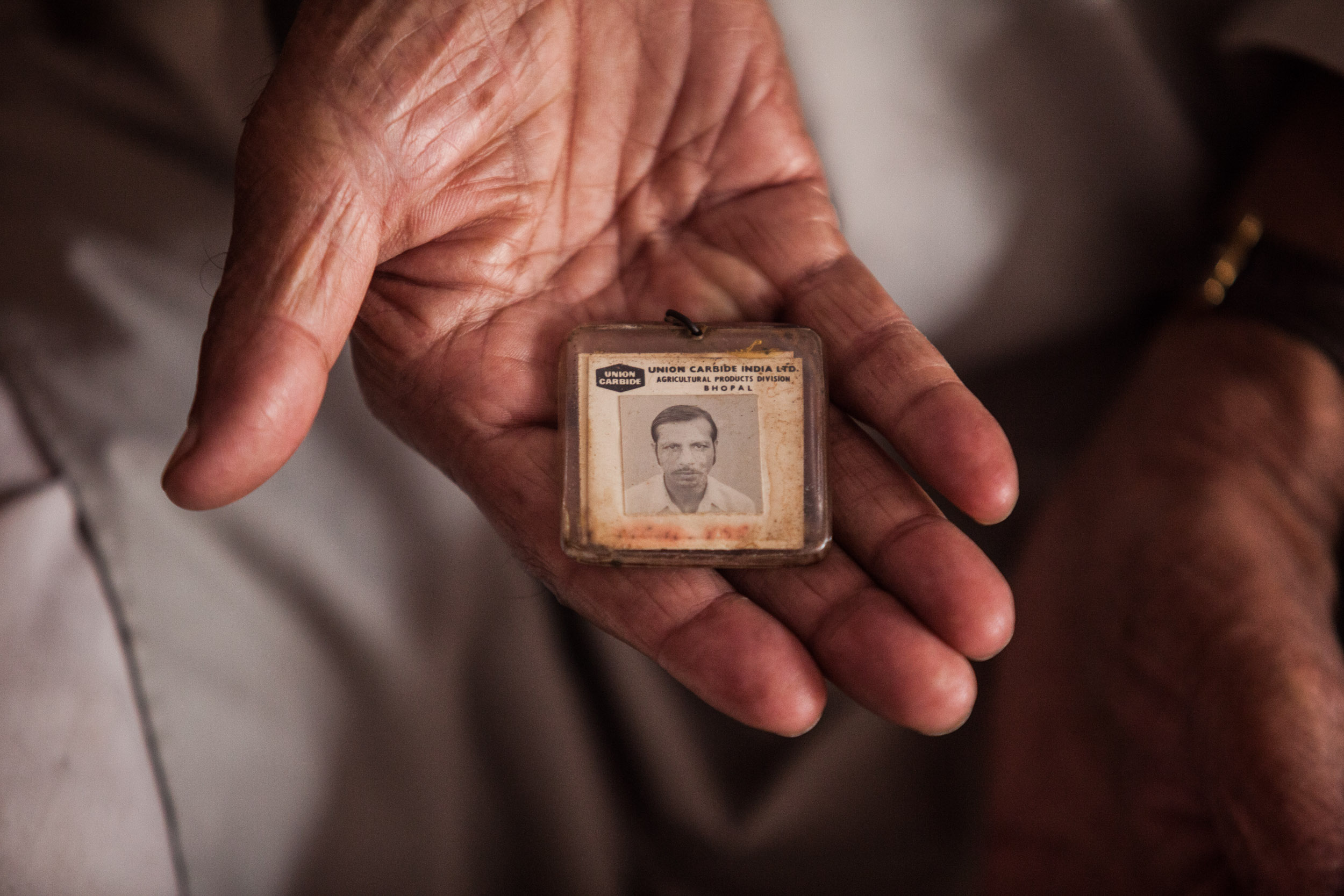 Mohammed Yaqub poses at home with his old Union Carbide card, which credited him as a factory worker