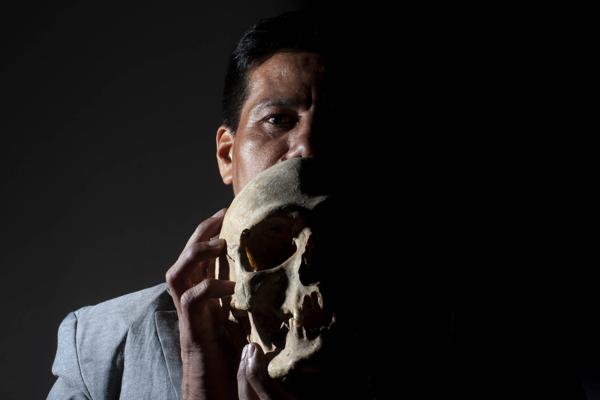 Israel poses for a portrait. He uses a human skull to conceal his identity.