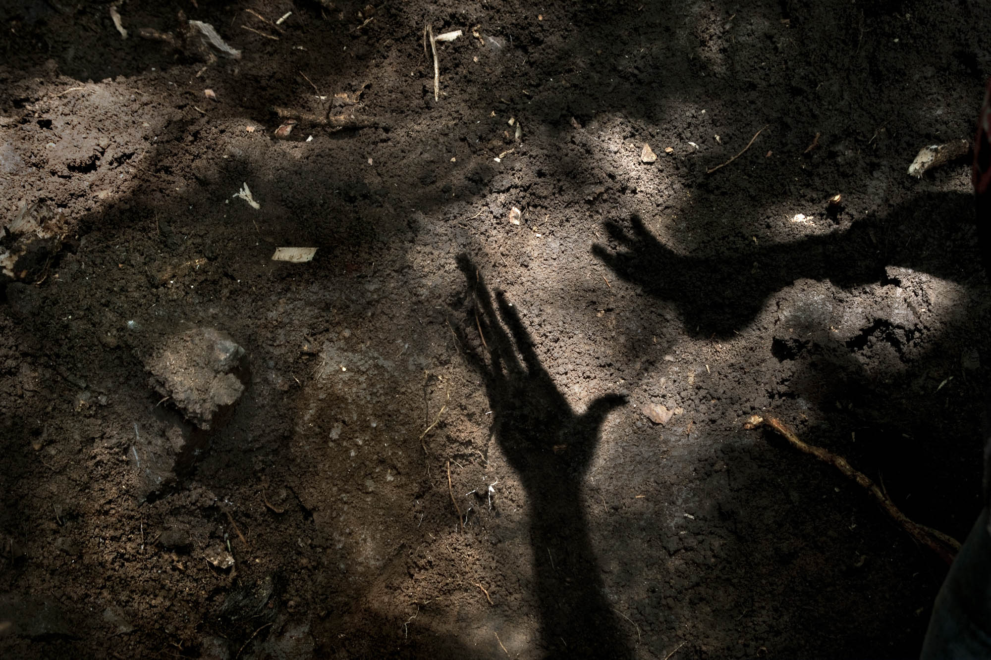 Israel projects his hands in the ground where he plans to dig searching for the body of William.