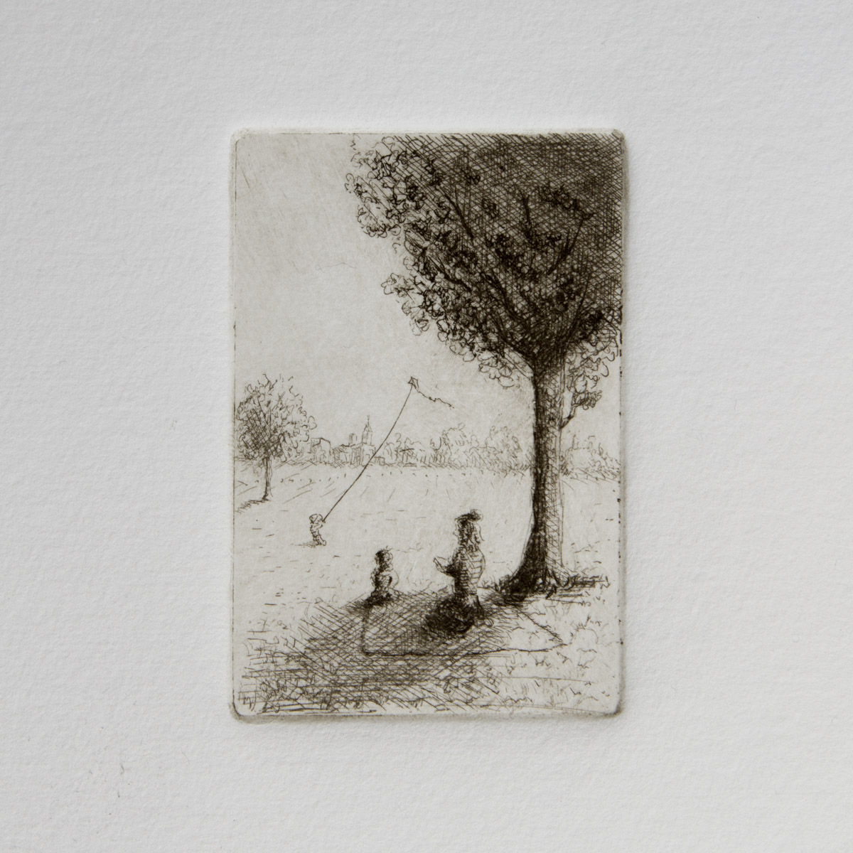 "Spring in the Park - 2019 (Etching)  $100-$150   ""A young mother spends a warm spring afternoon with  her children enjoying the shade of a tree. The older of the children fly  their kite in the gentle breeze. Reciting along with a favorite story,  the younger child sits patiently on a handwoven blanket. When the story  reaches its conclusion, the sun will have shifted, and their shade will  be gone. It will then be time to roll up the blanket and stroll home for  supper. """