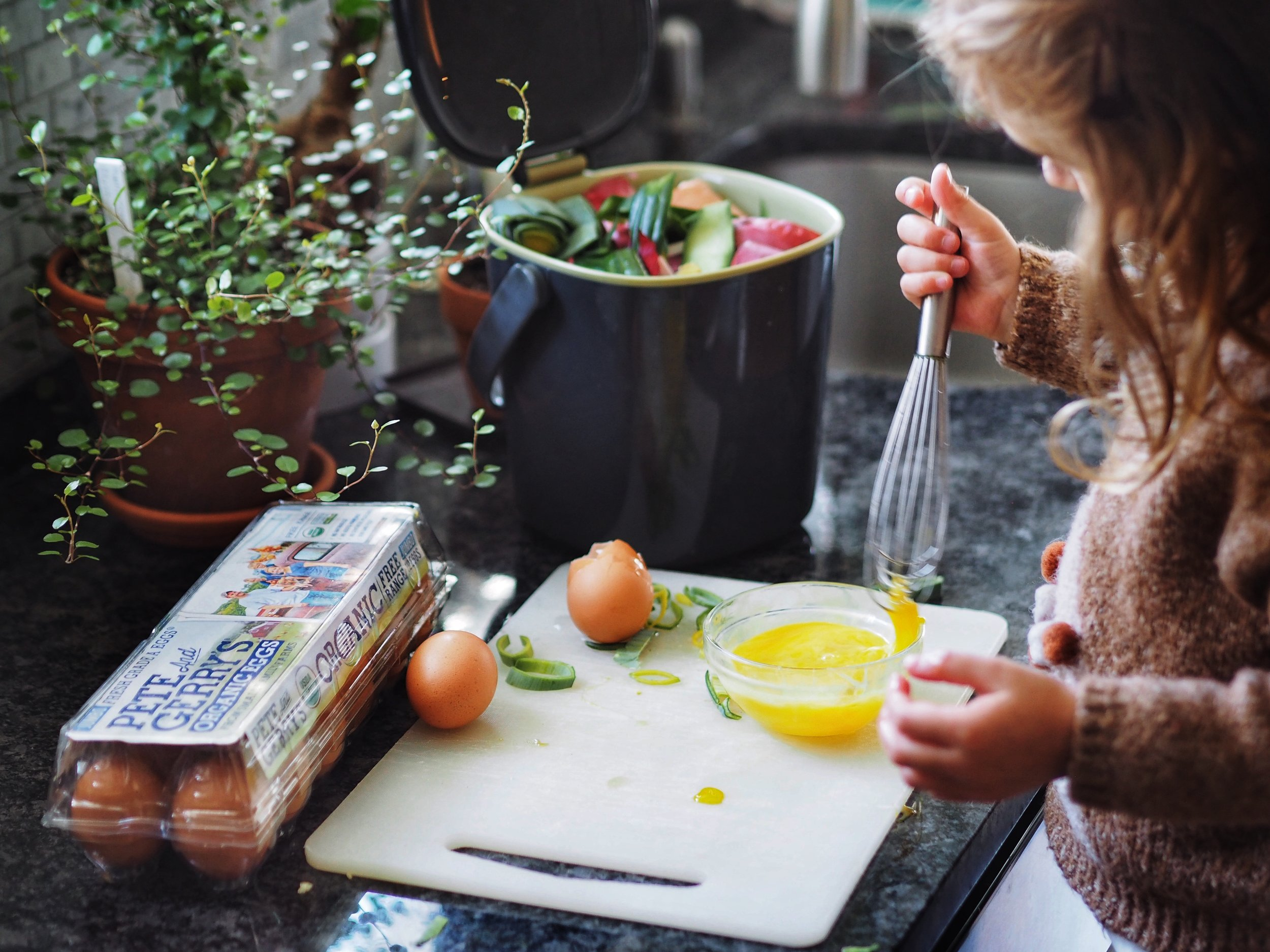 """You can use composting as a teaching opportunity for kids! Luci loves gathering our """"green"""" material to add to our bin, and I love seeing her grow more aware of nature's processes and cycles."""