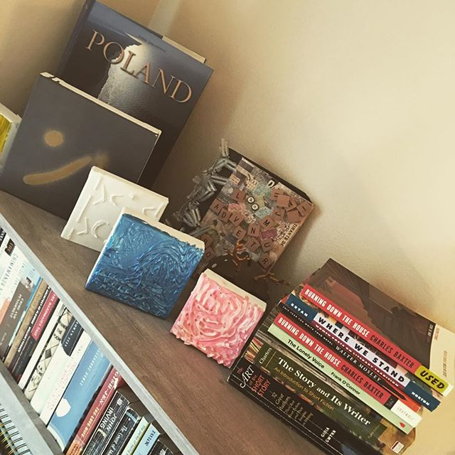 """Giveaway!! 📚📚 The top of my bookshelf is for art by my friend @elijah_fred and books about the writing process/craft! As you can see, I have two copies of """"Burning Down the House"""" by Charles Baxter. If anyone is looking for an amazing book about the writer's life and craft in general, let me know and I'll send it your way as a gift! The first person to DM me, can have it:)"""