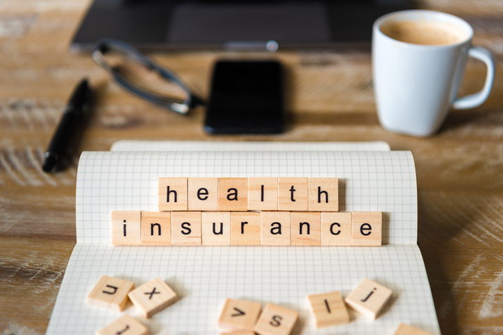 """Wooden tiles that spell out """"health insurance."""""""