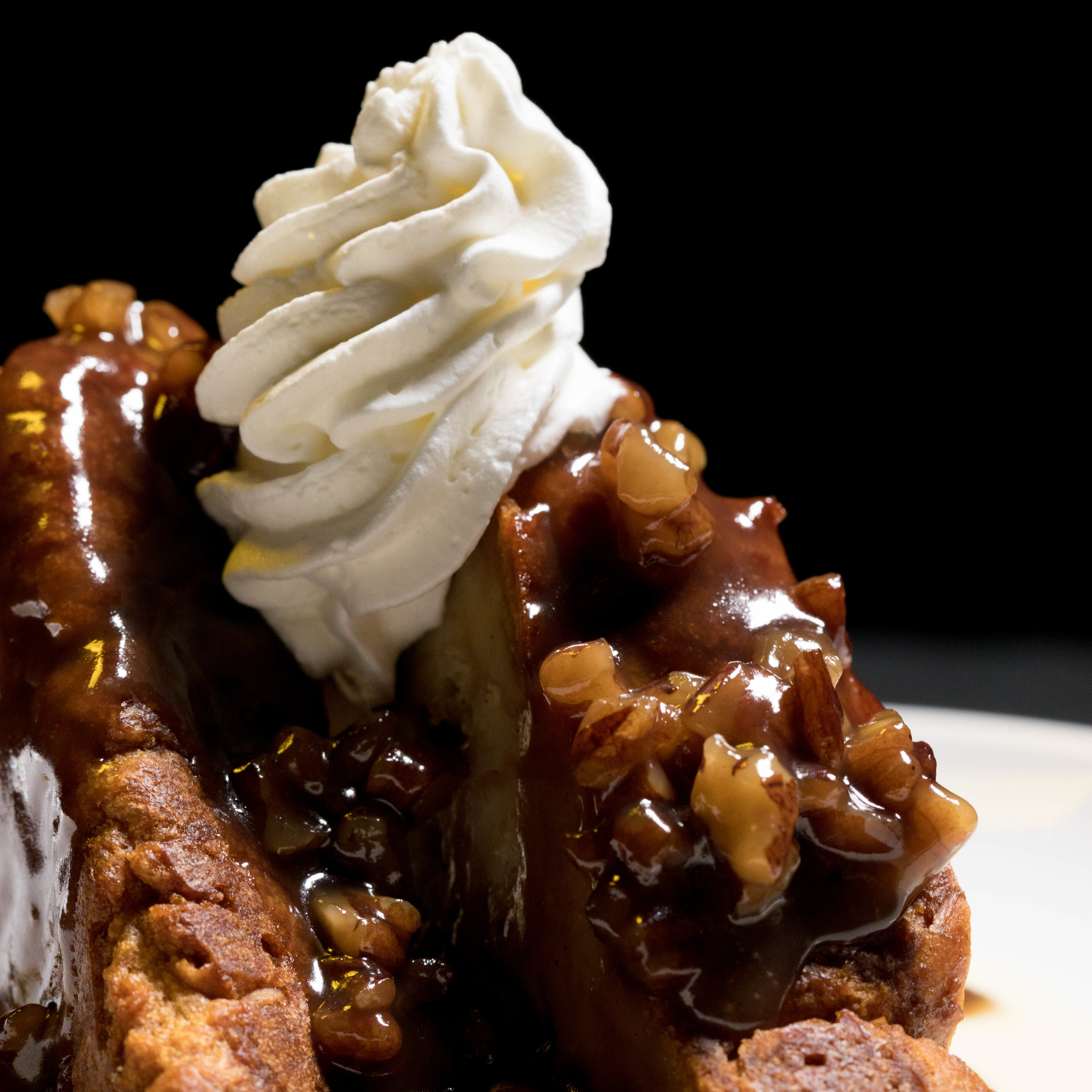 Praline French Toast |  fresh baked bread pudding on an anglaise sauce topped with a heated pecan praline sauce and whipped cream