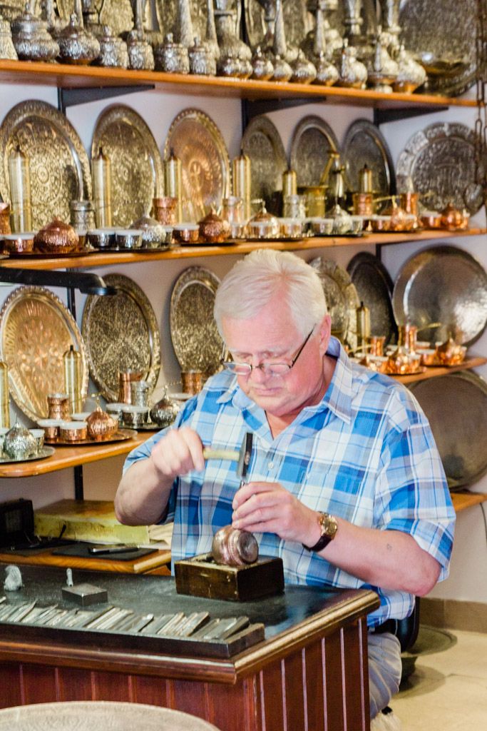 Local artisan in Sarajevo working on metal engraving. We purchased a silver platter as seen behind him and have it hanging on a wall.
