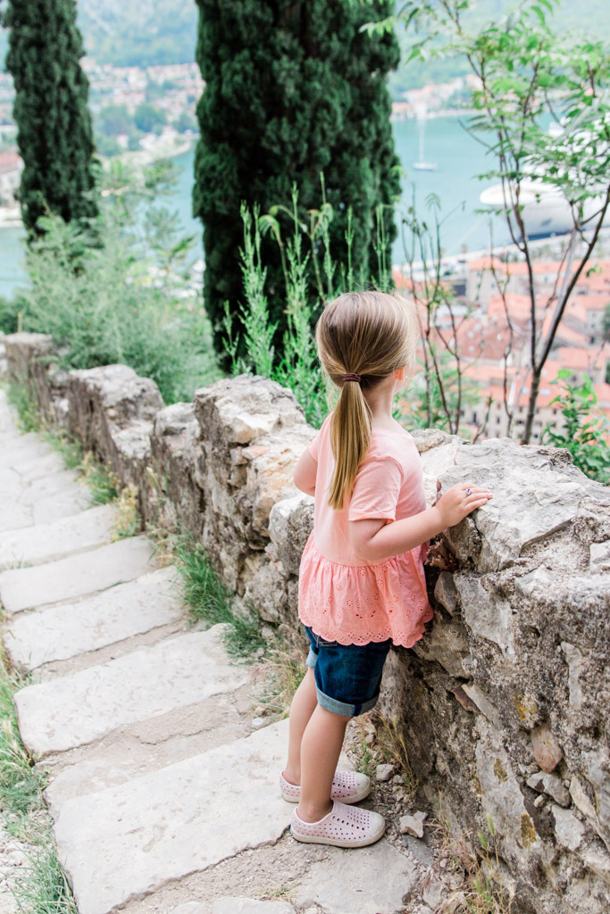 Little girl looking at the view from hiking the city walls of Kotor, Montenegro.