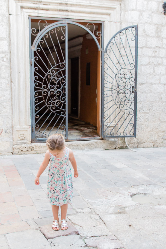Little girl standing on white stones in front of decorative iron gate in Kotor, Montenegro.