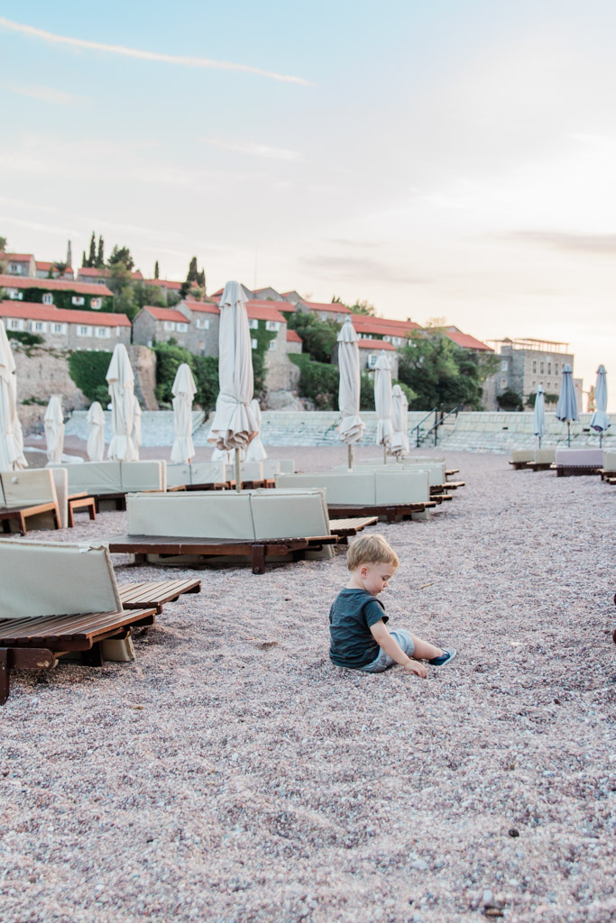 Baby boy sitting on pink rocky beach at sunset with lounge chairs and umbrellas in Sveti Stefan, Montenegro.