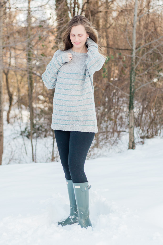 Woman 32 weeks pregnant standing in snow wearing gray maternity sweater, leggings, and Hunter rain boots.