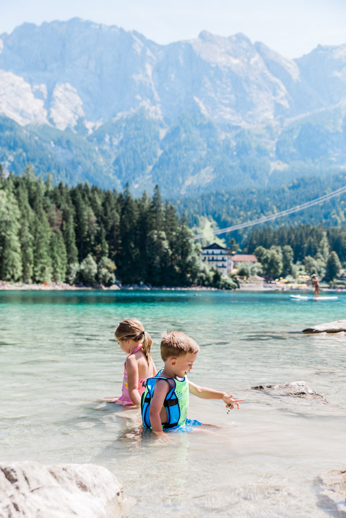 The kids swimming at Eibsee in the clear blue water. The Zugspitze sits right beside the lake.