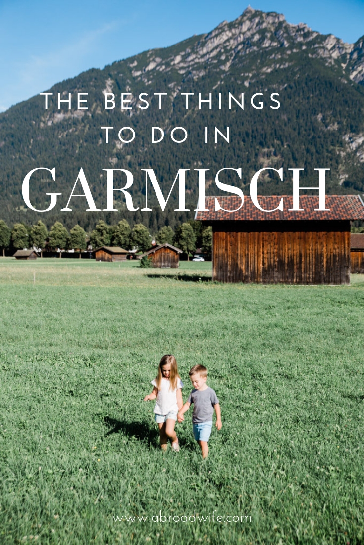 """Two children walking in grass field below mountains in Germany. Text overlay """"The Best things to Do in Garmisch"""""""