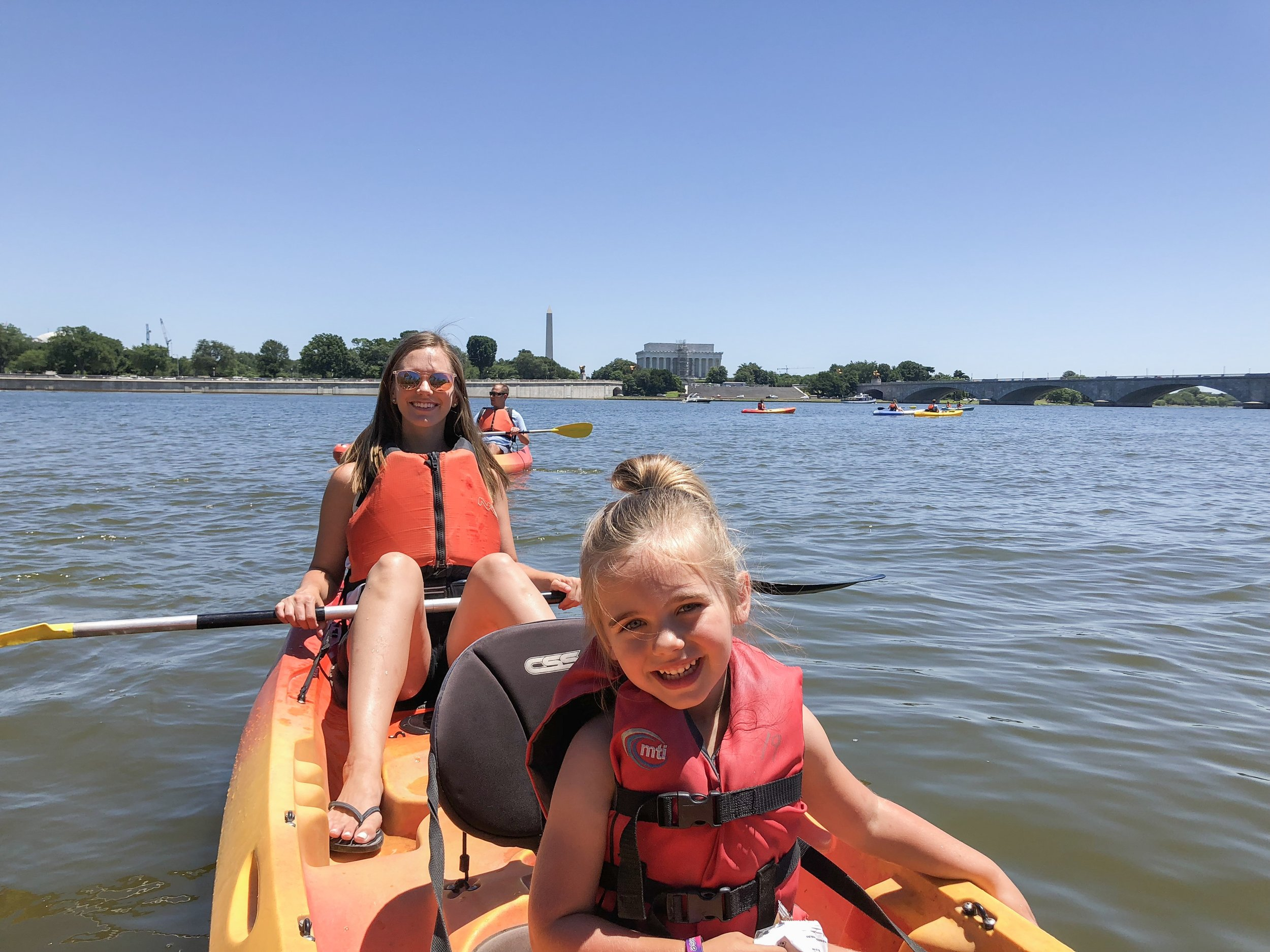 Mom and daughter kayaking in Washington D.C. with Washington Monument and Lincoln memorial in the background.