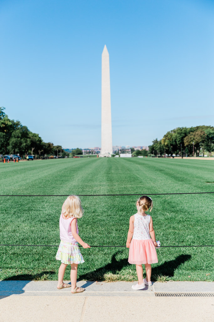 Girls looking at the Washington Monument on a summer day at the National Mall.