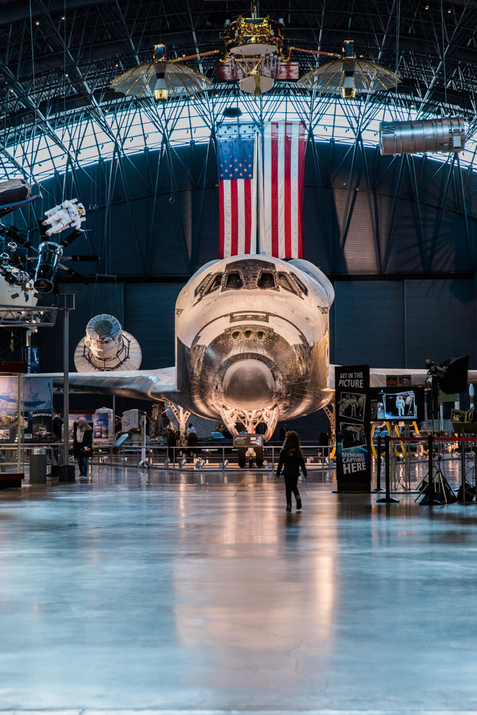 My daughter walking up to the space shuttle Discovery at the Udvar Hazy Center to take a closer look.