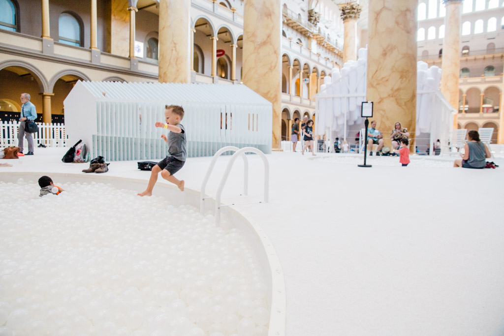 Little boy jumping into giant white ball pit in the National Building Museum.
