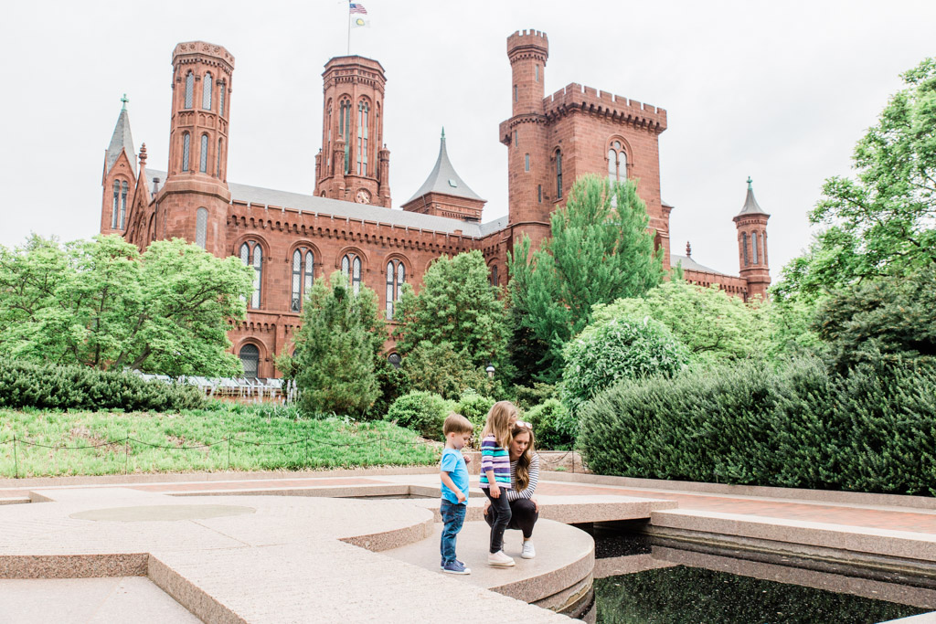 Mom and kids looking in a pond with red-bricked Smithsonian Castle in the background.