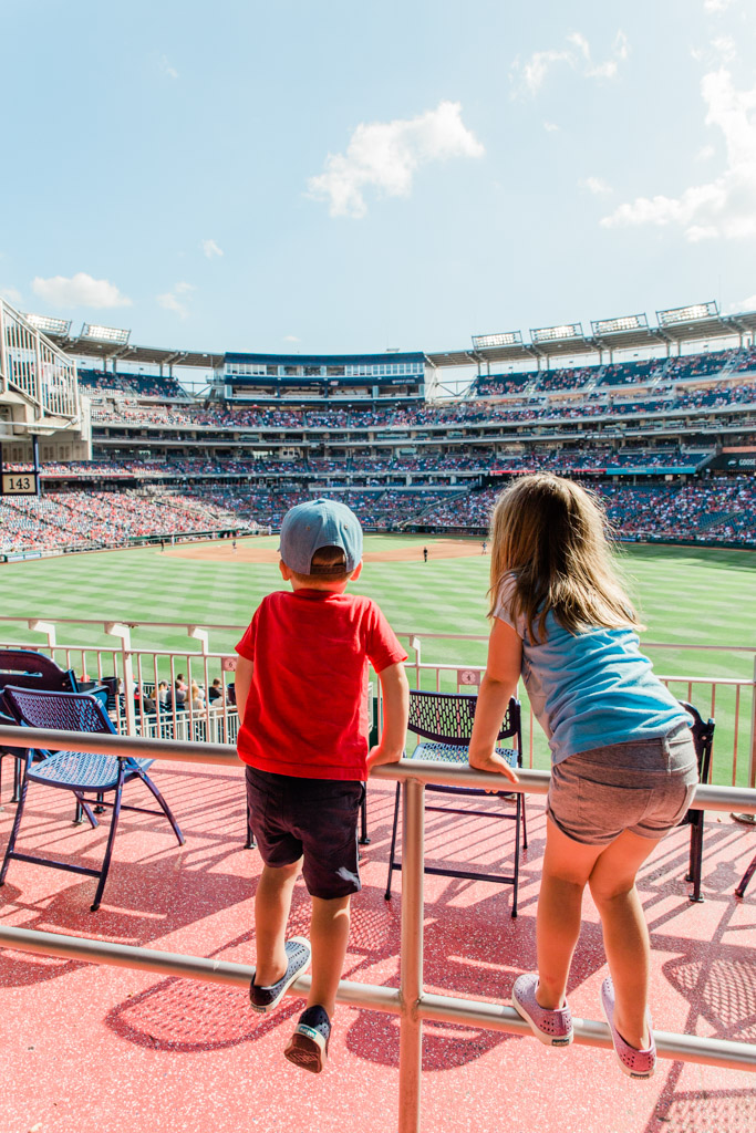 Kids standing on the railing looking out at the Washington Nationals baseball game.
