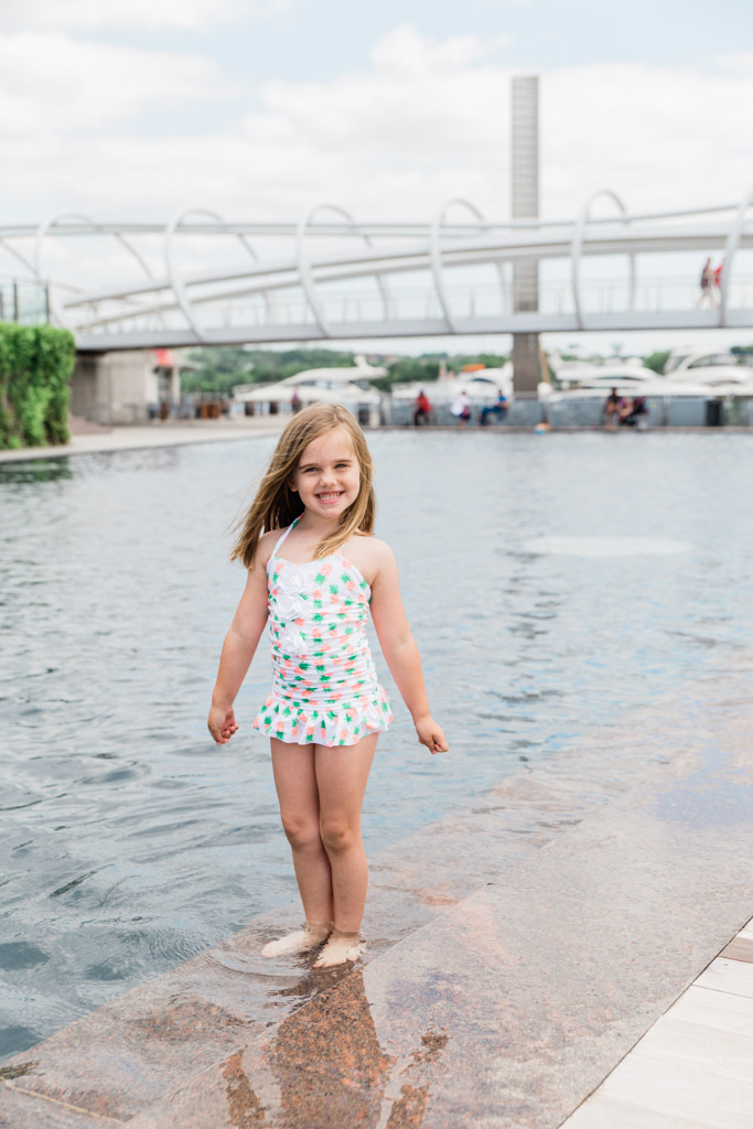 Little girl in pineapple bathing suit wading in water at Yards Park, Washington D.C.