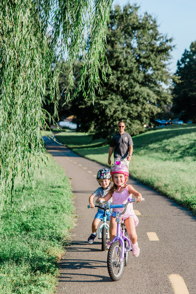 Little girl in a princess helmet and little boy riding bikes on the Mount Vernon trail.