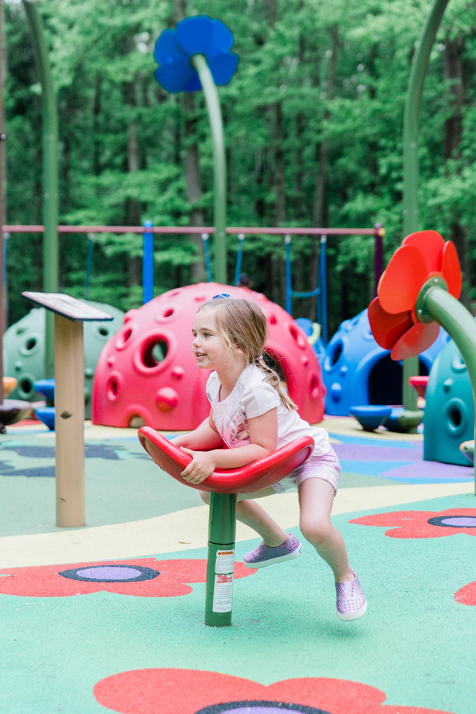 Little girl playing on spinning flower on colorful playground.