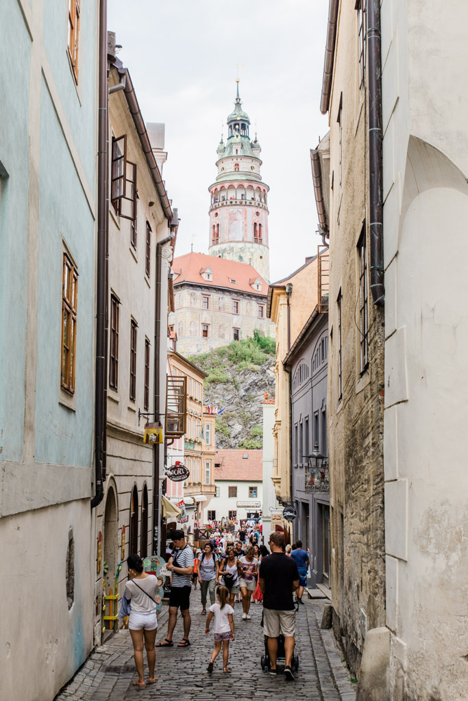 Crowded cobblestone alley leading to painted Baroque Tower in Cesky Krumlov.