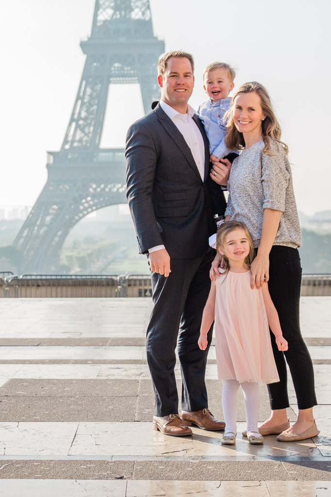 Family of four with a little girl and little boy smiling in front of the Eiffel Tower in Paris.