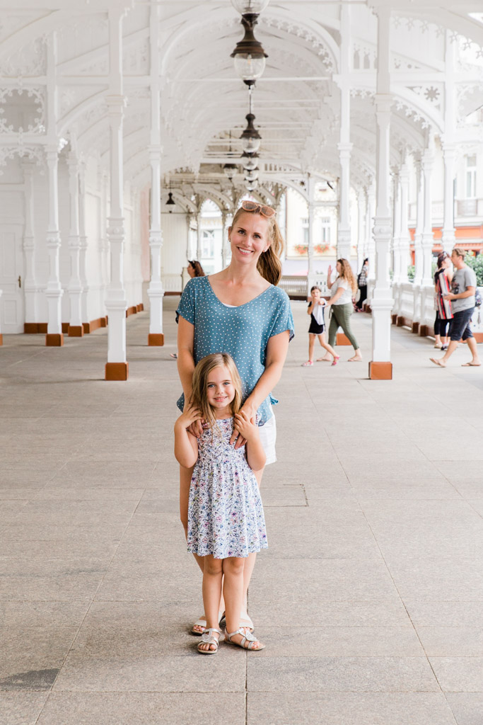 Mother and daughter in white carved colonnade in Karlovy Vary.