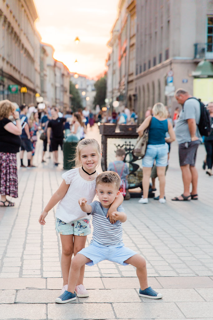 Young girl with her arm around her little brother at sunset in the main square of Krakow.