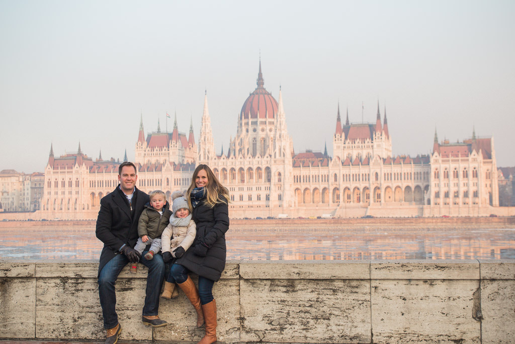 Family of four sitting on river bank across from Hungarian Parliament Building in Budapest.