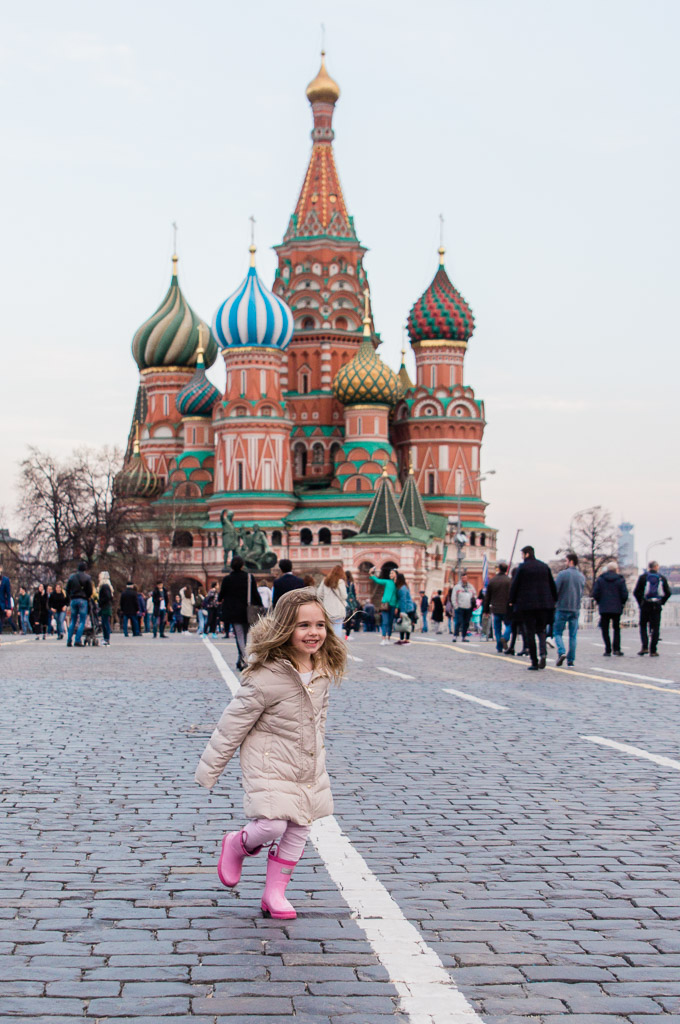 Little girl in pink rain boots and a winter coat running in front of St. Basil's Cathedral in Moscow, Russia.