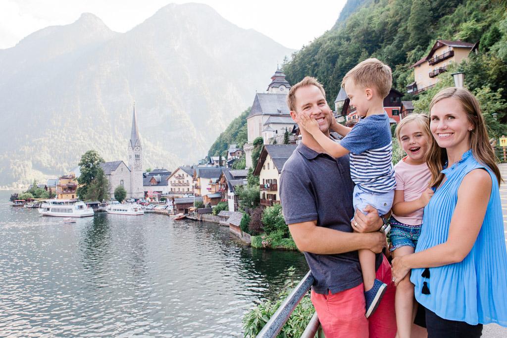 Family of four posing in front of lakeside European town of Hallstatt, Austria in summer.