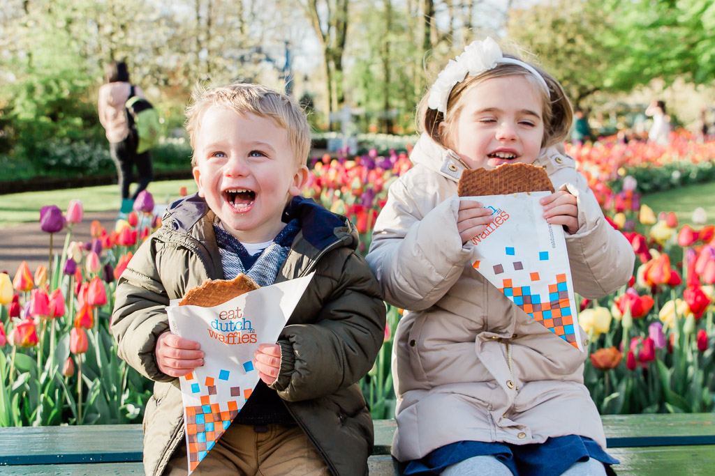 Little boy holding a stroopwafel laughing with little girl taking a bite out of a stroopwafel in a colorful tulip garden.