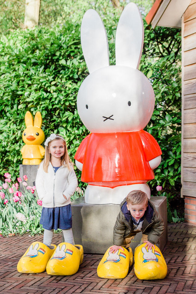Little girl and little boy standing in large yellow clogs in front of giant white bunny in a garden.