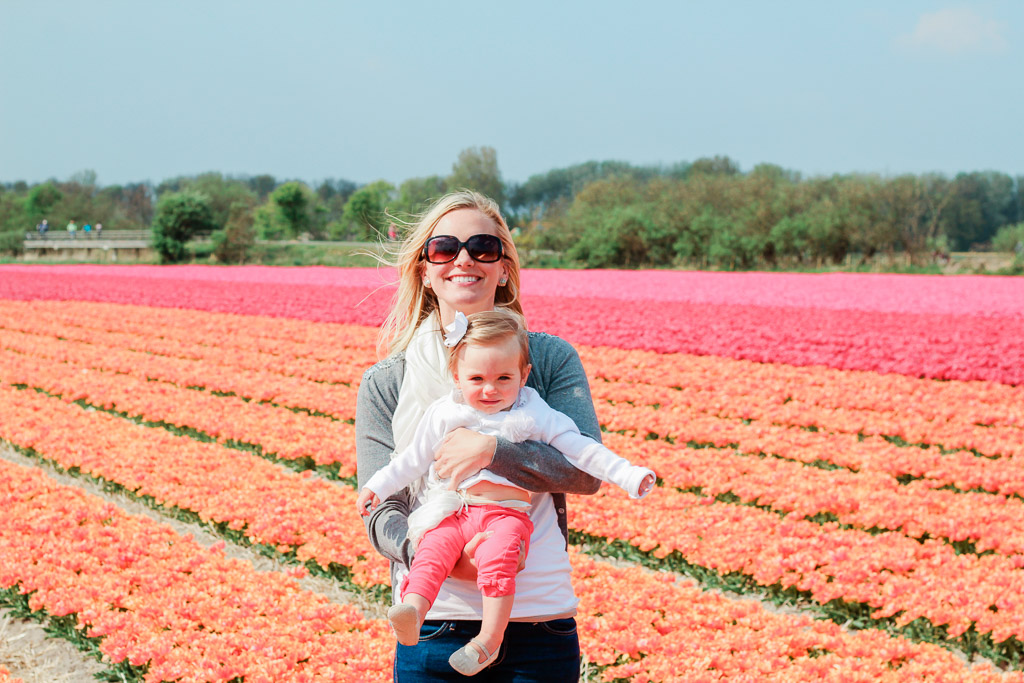 Woman in sunglasses holding one year old daughter in orange and pink tulip fields.