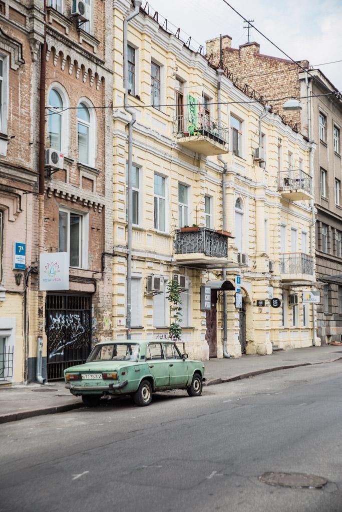 Green old Soviet car parked on a street in Kiev.