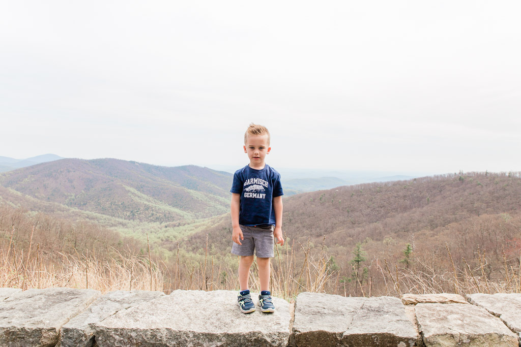 Little boy standing on a rock wall with Blue Ridge Mountains behind him at Shenandoah National Park