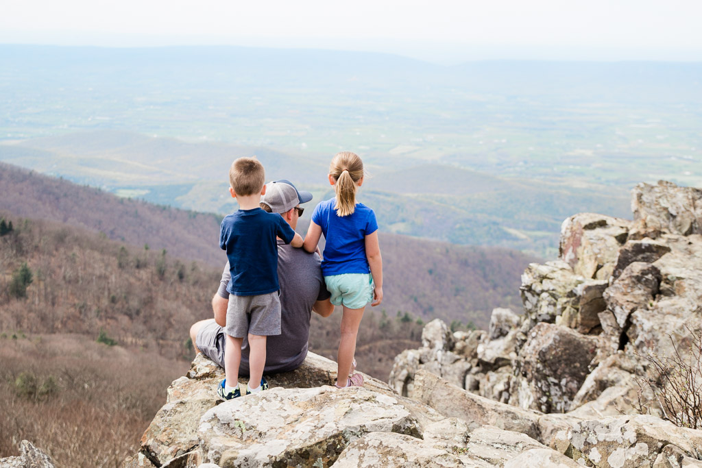 Father sitting on a rock with son and daughter standing behind him overlooking the Shenandoah Valley.