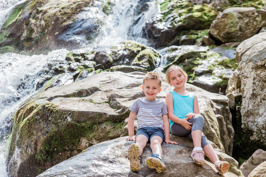 Little boy and girl sitting on a rock in front of waterfalls at Dark Hollow Falls in Shenandoah National Park.