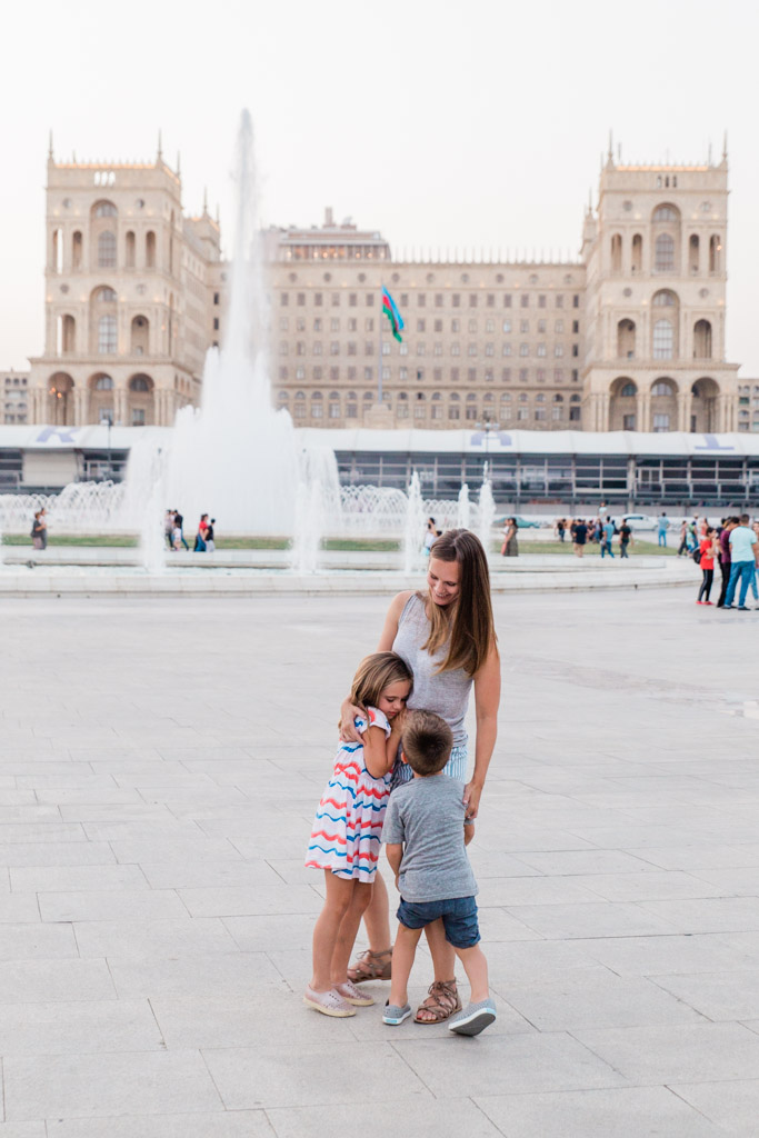 Mom hugging daughter and son in front of a large fountain with a big European looking government building in the background in Baku, Azerbaijan.