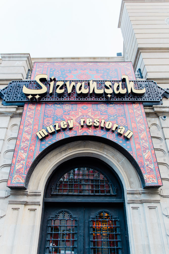 Black wrought iron doors and colorful sign of restaurant.