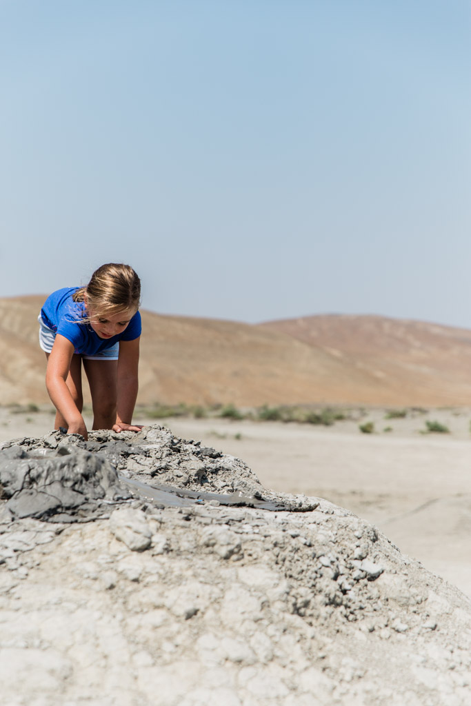 Little girl in a blue shirt putting her hands into a mud volcano in Azerbaijan