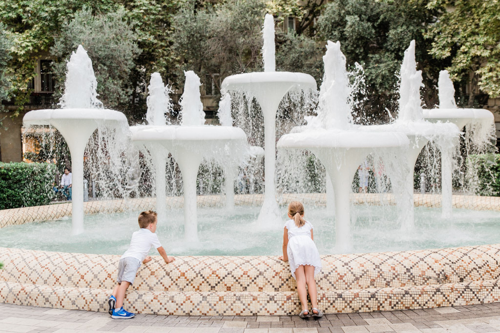 Little boy in a white shirt and little girl in white dress leaning over the edge of a large fountain in Baku, Azerbaijan.