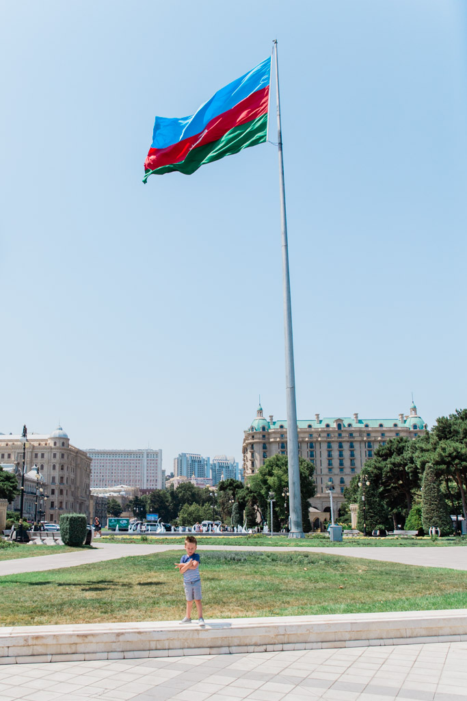 Little boy in shorts and t-shirt standing in front of a huge flagpole flying the flag of Azerbaijan with the city in the background.