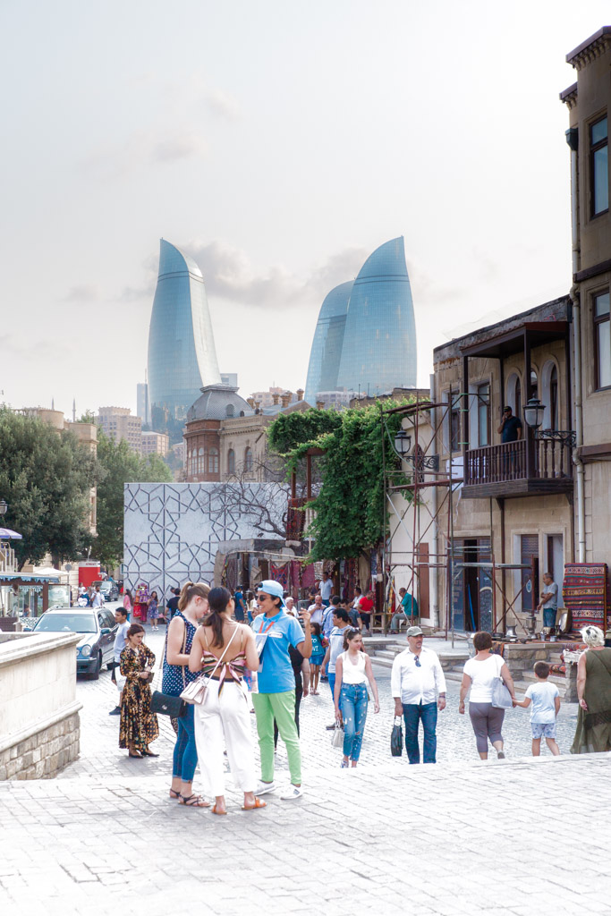 People walking through Old City Baku with the flame towers in the background.