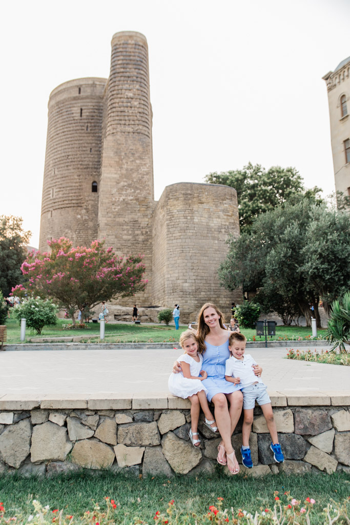 Mom sitting on rock wall with daughter and son in front of an old stone tower in Old City Baku.