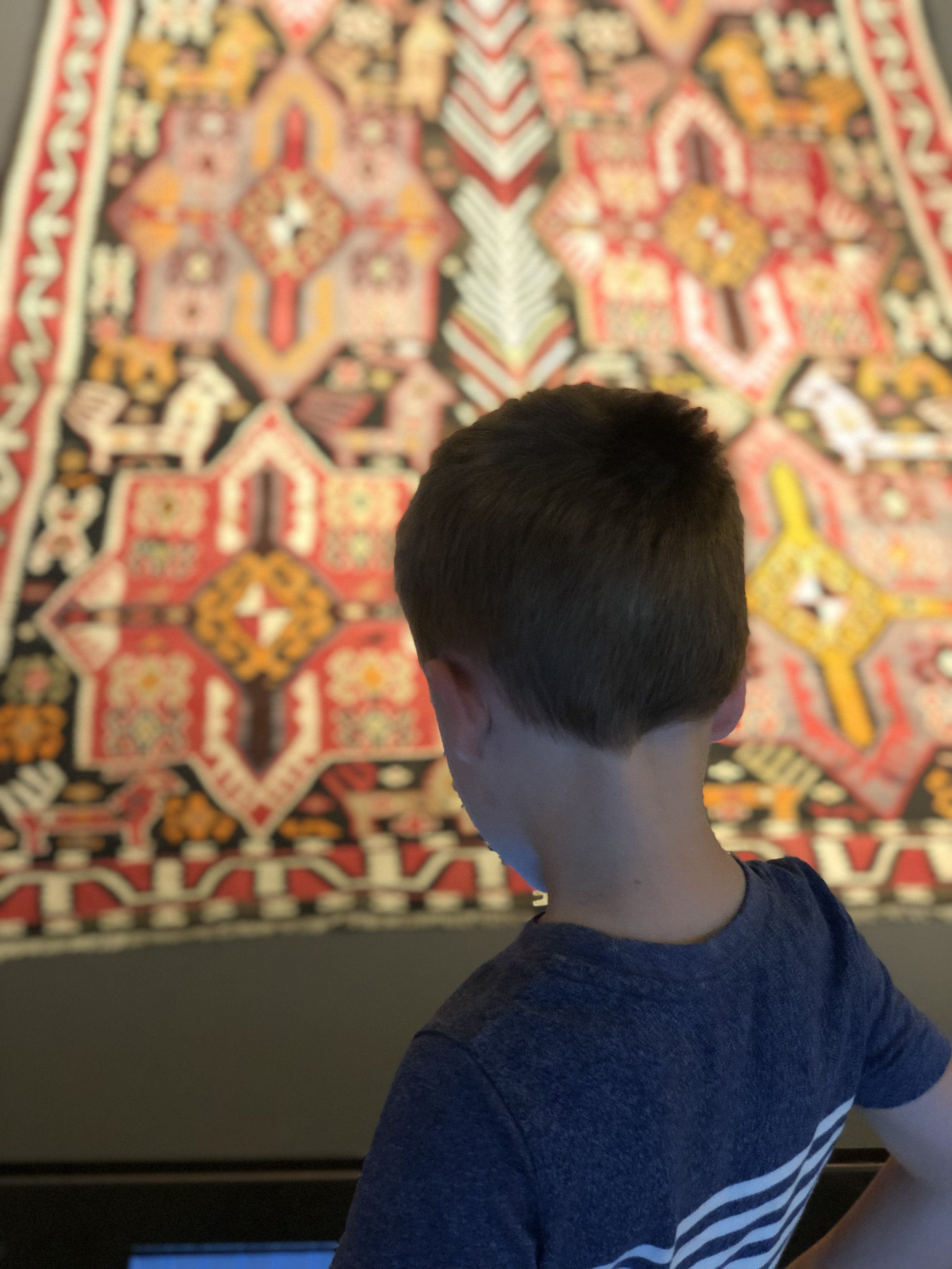 Photo taken behind a little boy who is looking at a giant, colorful Azerbaijani carpet.