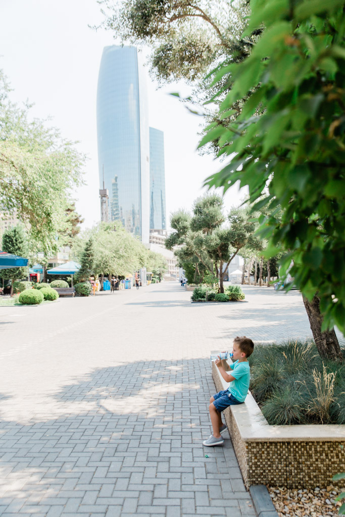 Little boy drinking from a water bottle sitting on the edge of a planter in a park with skyscraper in the background.