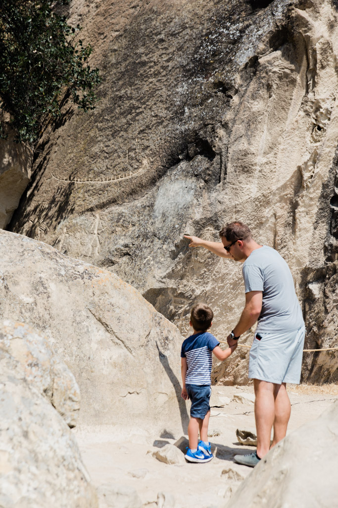 Father pointing at cave drawings on rocks to show a little boy.