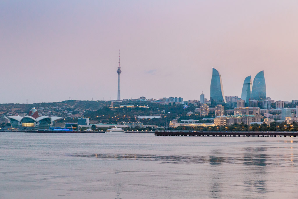 Caspian Sea in the foreground with the Flame Towers and TV Tower in the Baku skyline at sunset with a purple sky.